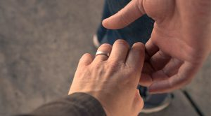 Spouses touching hands with an Original simple ring.