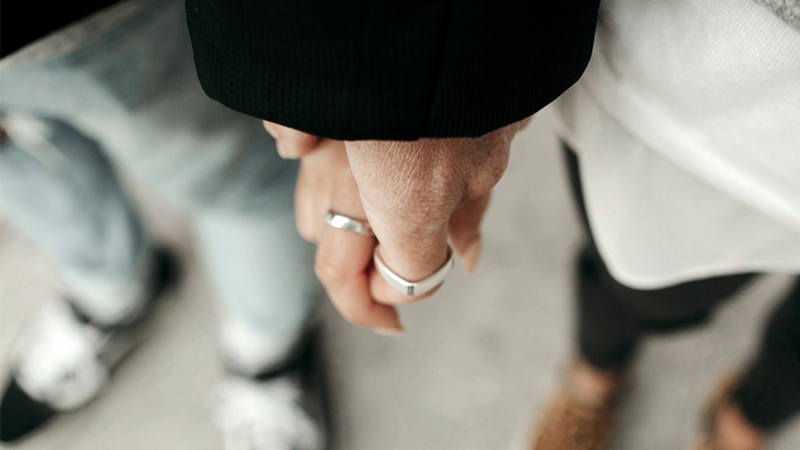 Hands clasped wearing rings.